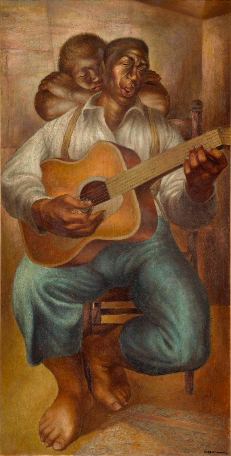 A seated man is performing at the guitar while a woman rests her head in her arms behind him
