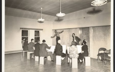 Black and white image of Charles White teaching a life drawing class to eight students in Chicago