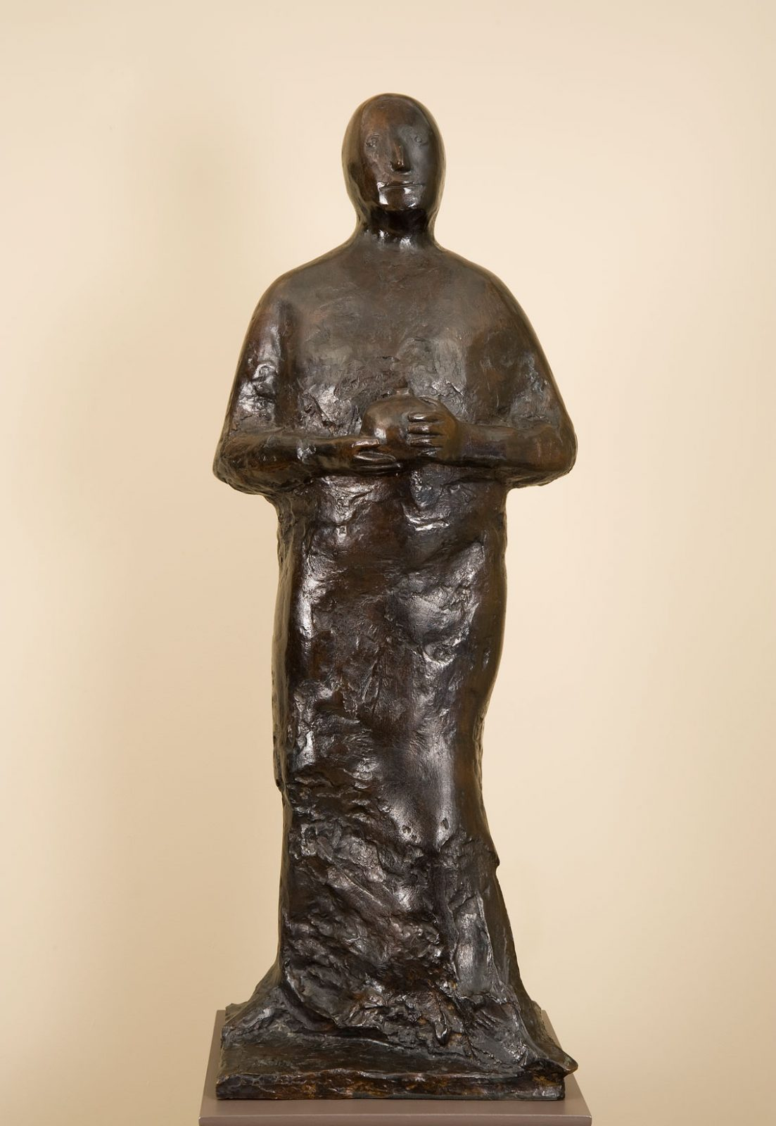 This bronze by Leonard Baskin shows a standing man holding a pomegranate with two hands