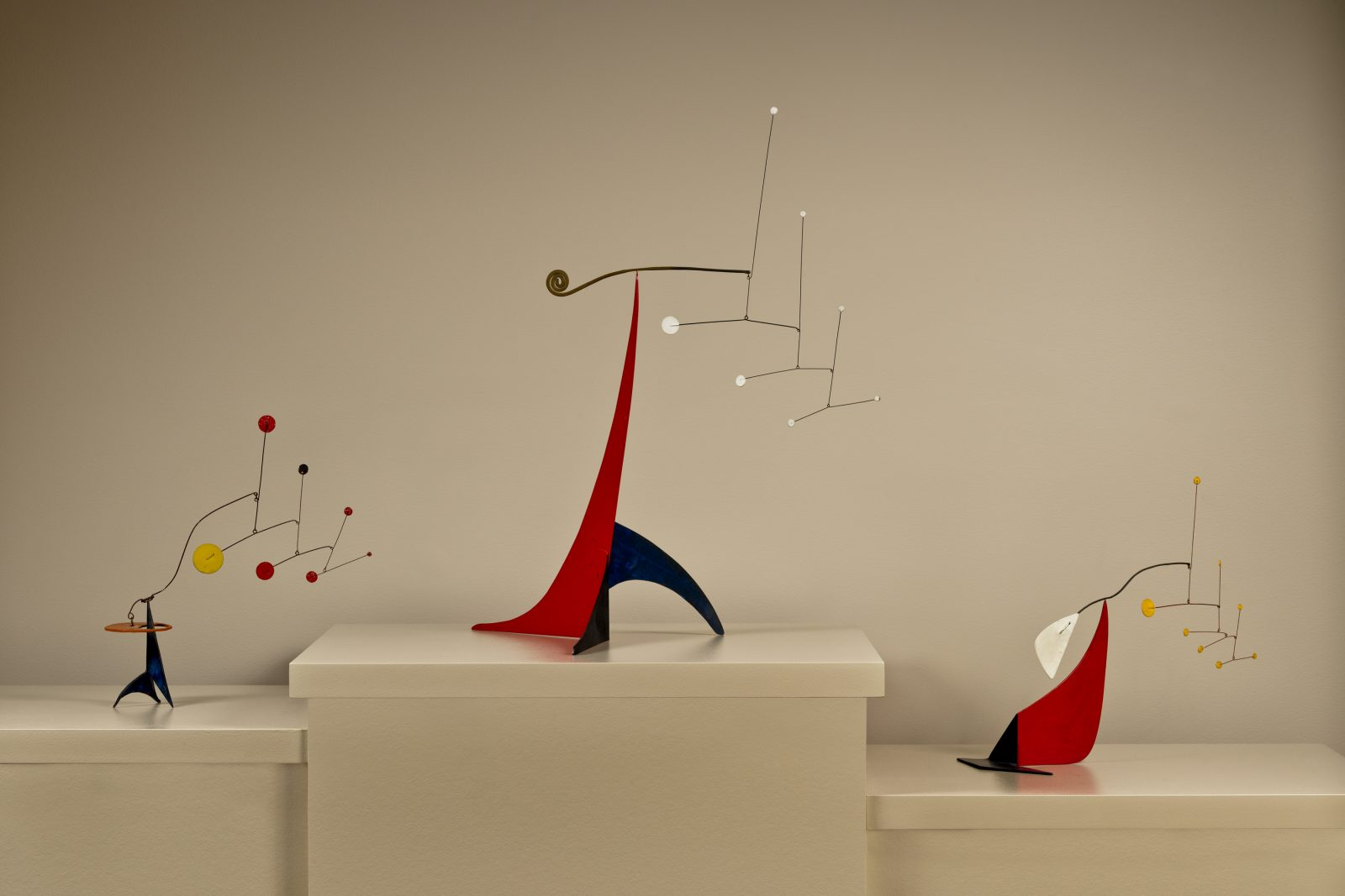This photograph shows three colorful mobiles by Alexander Calder.