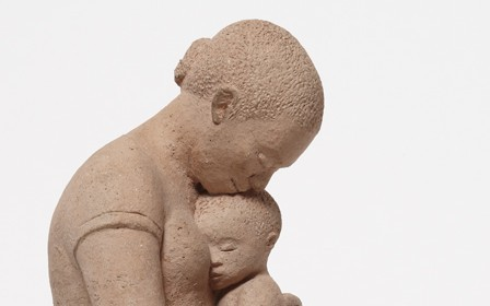 This work by Elizabeth Catlett shows a mother looking down and nestling the head of the child