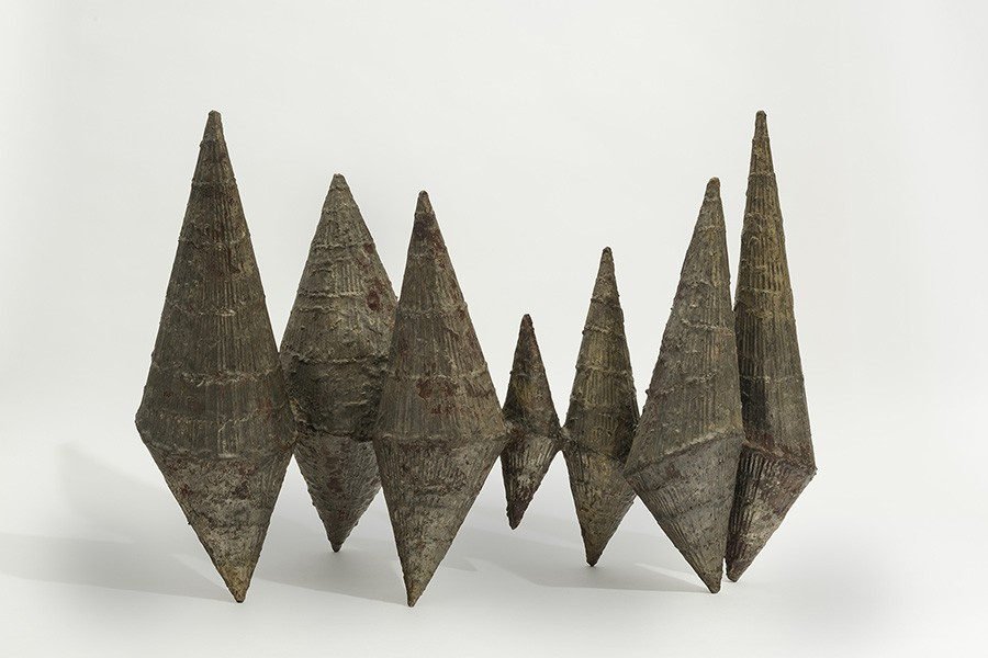 The present sculpture consists of seven cone-shaped abstract forms. Each cone is unique in size, patina, and texture due to the individual nature of the welded wires and melted brass.