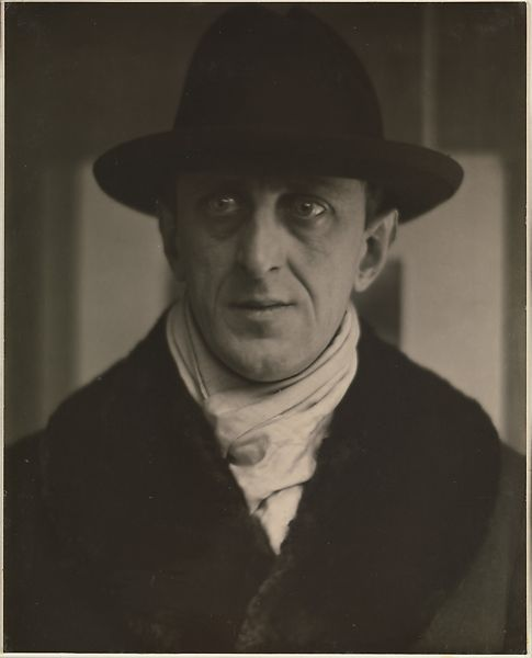 Photograph of Marsden Hartley wearing a black, bowler hat, white scarf and black coat.
