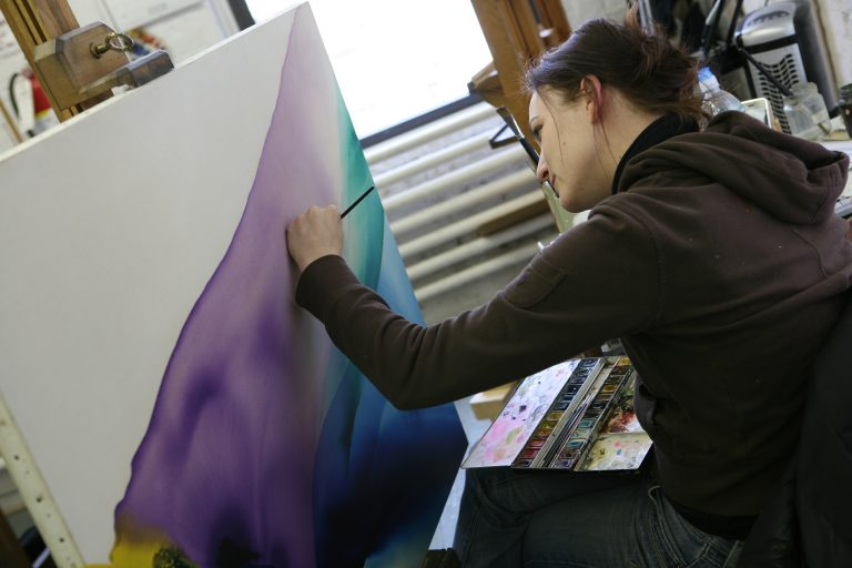 Lowy Senior Paintings Conservator Lauren Rich in-painting a modern artwork.