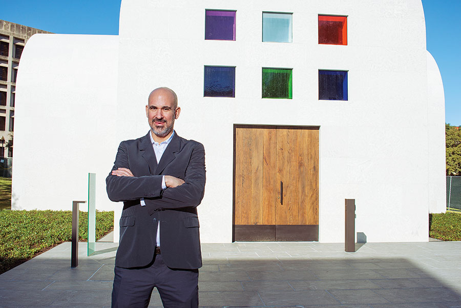 Blanton Museum Curator Carter E. Foster stands with his arms folded in front of the Ellsworth Kelly Chapel in Austin, Texas.