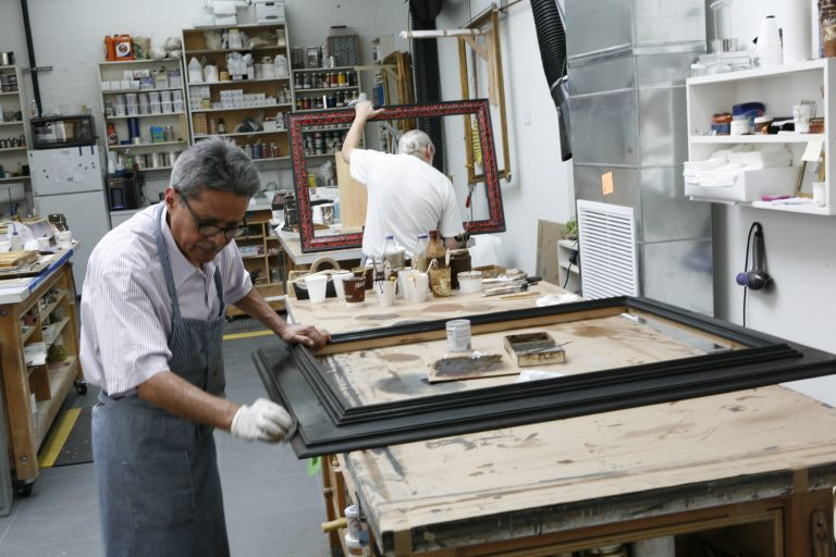 A Lowy framer polishes a reproduction frame.