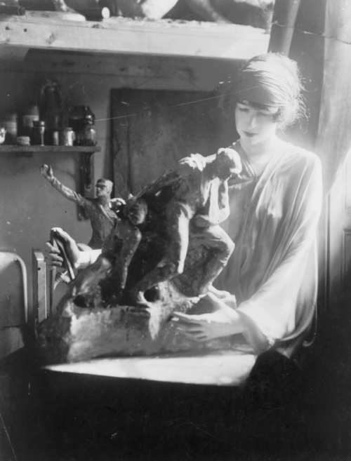 A photograph of Gertrude Vanderbilt Whitney in front of her sculptural series of soldiers
