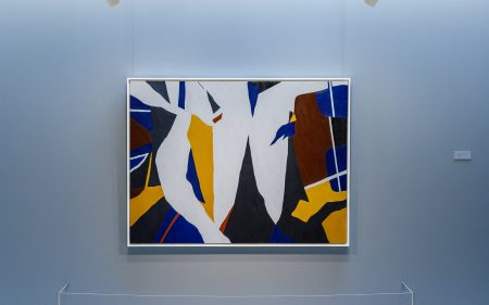 """Install image of Ralston Crawford's """"Torn Signs"""" painting with a viewing bench placed in front."""