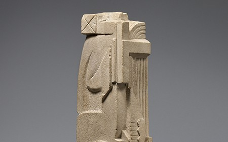 In this sculpture by José De Creeft, art deco motifs, geometric forms, and a stylized African mask adorn the surface of the stone