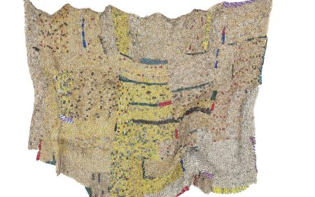 El Anatsui's tapestry made from aluminum and Cooper wire. Featuring golds, red, greens, blues, and yellows