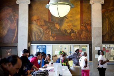 Mural by Ben Shahn in the main lobby of the Bronx General Post Office. Post office patrons congregate underneath.