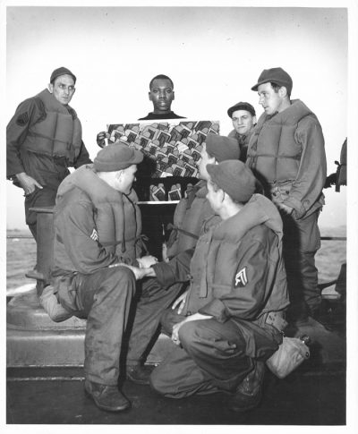 Black and white photograph showing Jacob Lawrence showing one of his paintings to six men in navy uniforms, gathered around him