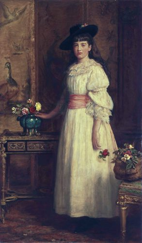 A portrait of a young Gertrude Vanderbilt Whitney standing in a white dress next to a vase with flowers.