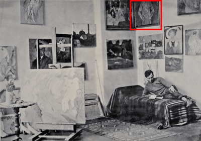 Albert Bloch reclining on his bed in the corner of his Munich studio. The walls are covered in paintings and an easel sits on the left..