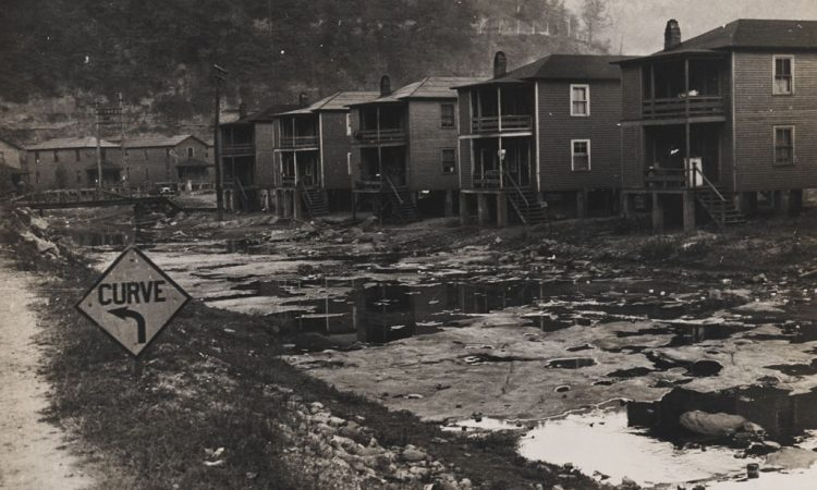 Black and white photograph by Ben Shahn showing a muddy road and some houses
