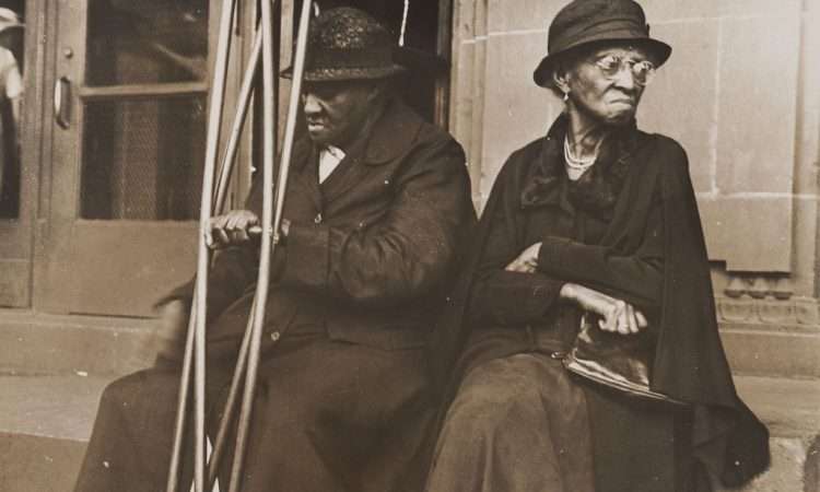 Black and white photograph by Ben Shahn showing two people sitting in front of the hospital