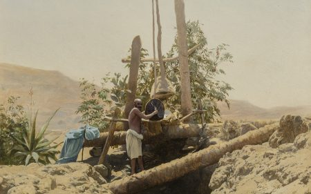 A man standing on top of a well in a desert.