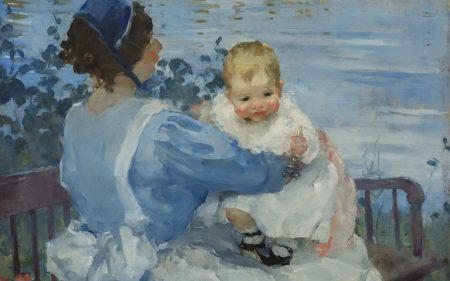 A nurse in blue holds a baby dressed in white. The two sit next to the water.
