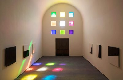 Interior of the Ellsworth Kelly Chapel, which has white walls and six square stained glass windows. Each stained glass window is a different color.